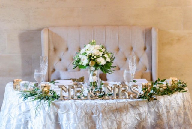 Sweetheart Table with Bridal Bouquet, Greenery, and Mr. and Mrs. Sign