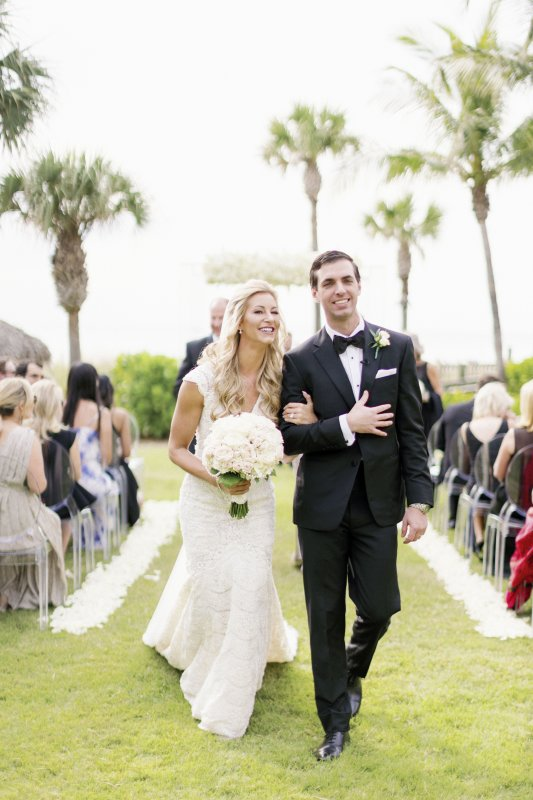 Bride with All-White Bouquet and Groom walking down aisle
