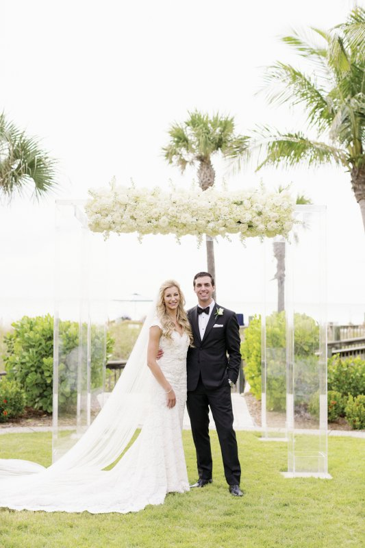 Bride and Groom in front of Beautiful Acrylic Canopy with White Flowers