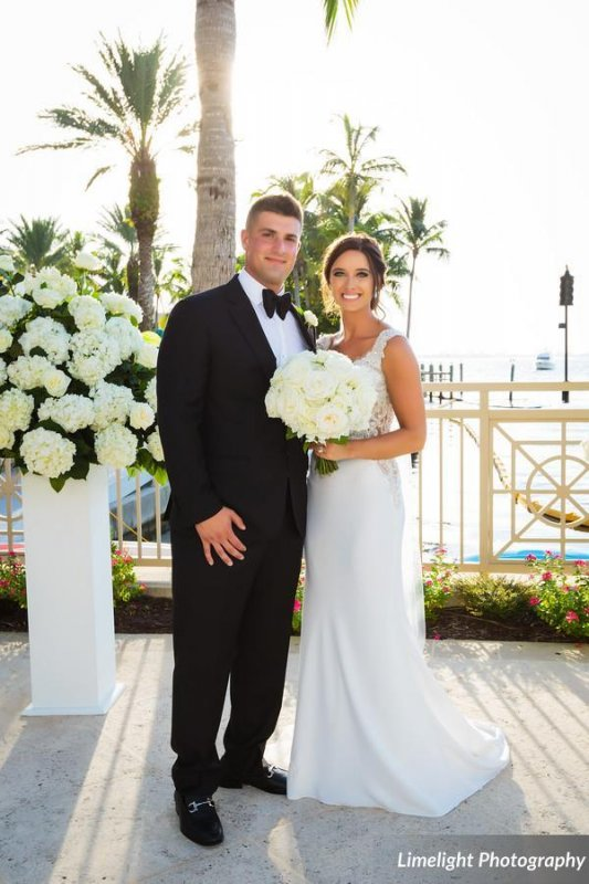 Bride and Groom next to gorgeous all-white floral arrangement on column Bayview Terrace Ritz Carlton