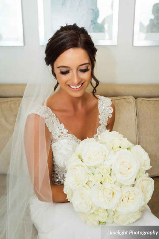 Bride with all white bouquet of spray garden roses and hydrangea