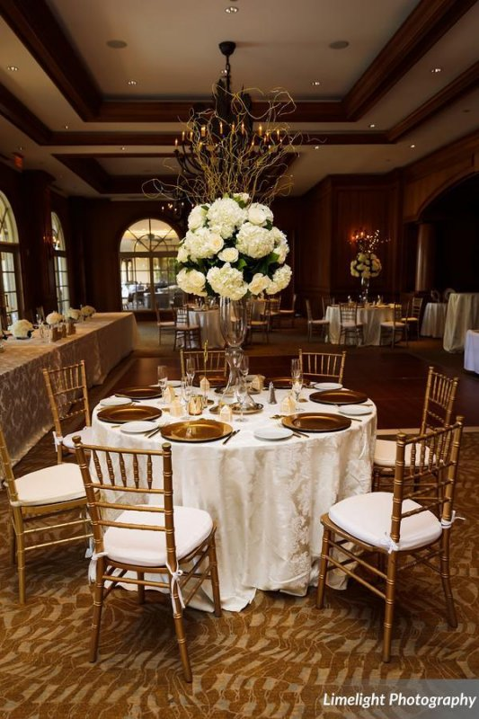 Elevated Guest Table Floral Arrangements of white hydrangea with curly willow and fairy lights