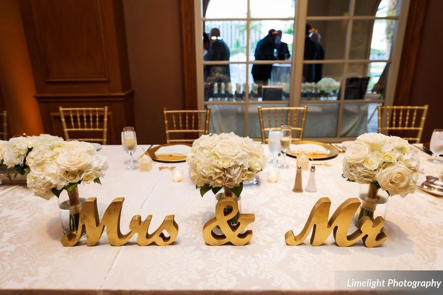 Head table with Mr. and Mrs. Sign and Bridesmaids' Bouquets in Vases