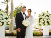 Bride and groom framed by all-white large columns on terrace