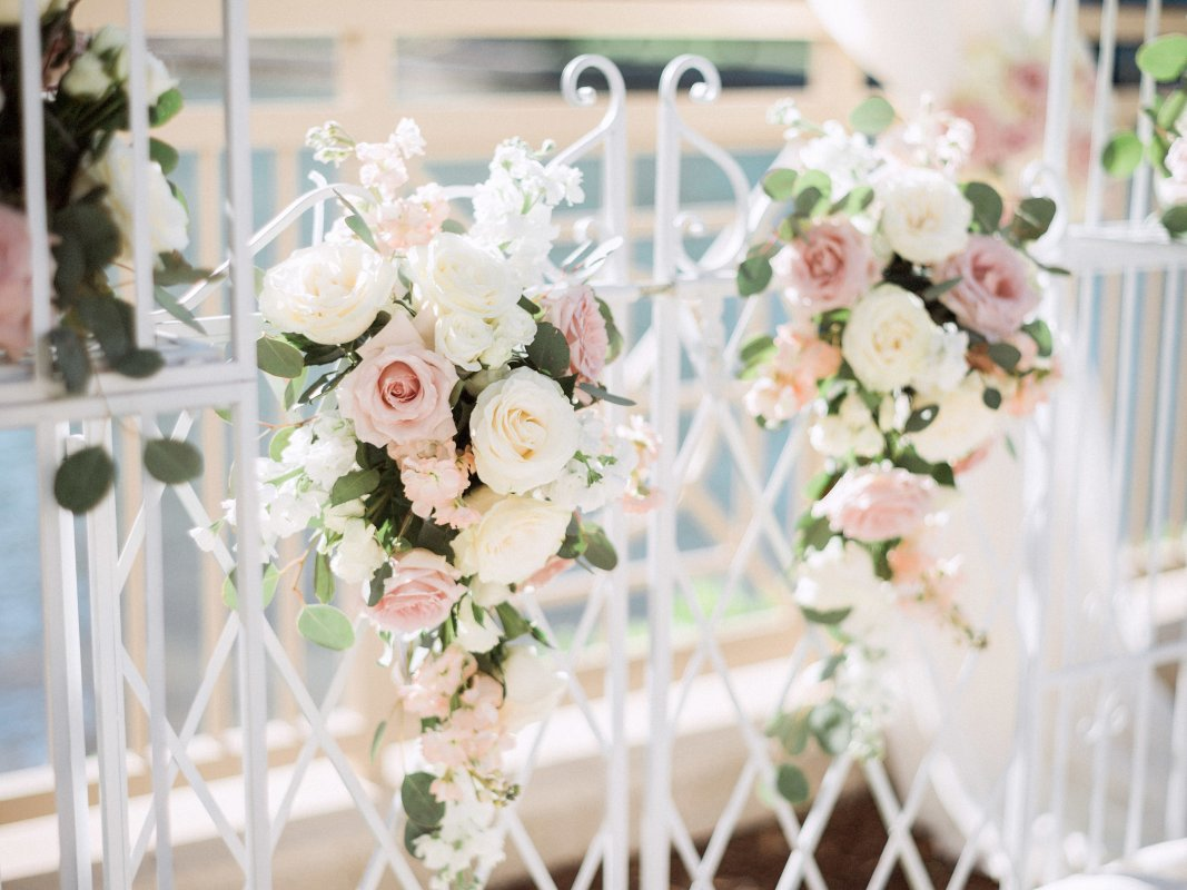 Floral sprays on arch with roses and silver dollar eucalyptus
