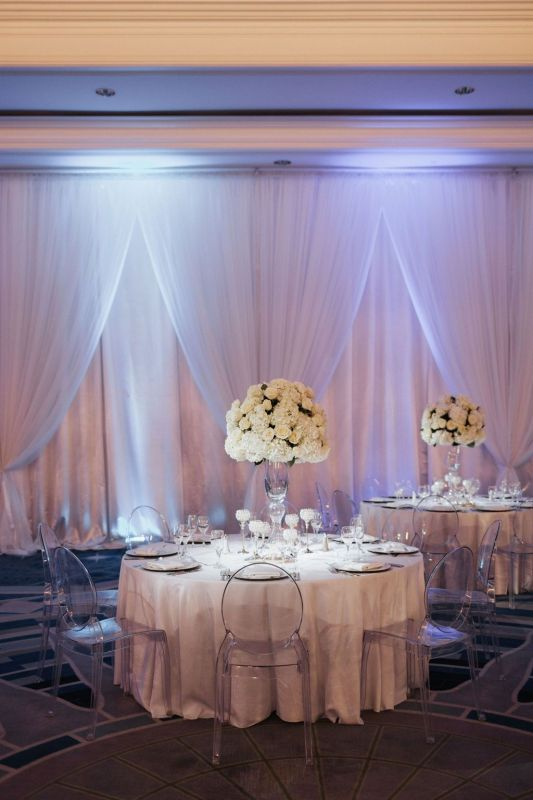Elevated Table Centerpieces with White Roses on Double Bell  Vases and White Draping
