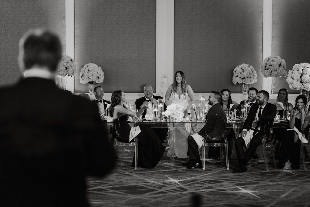 Black and White Photo of Head Table with Flowers from Ceremony Behind Table