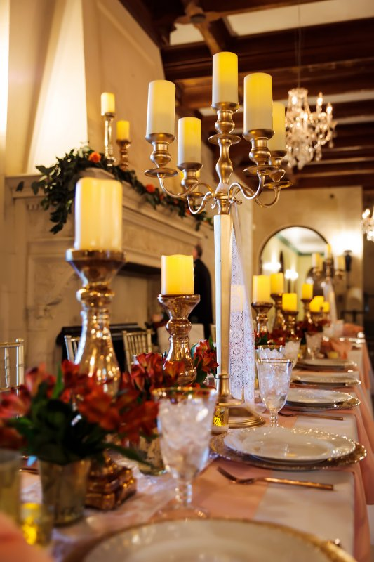Head Table with Tall Candelabara Low Gold Candle Holder and Lots of Small Arrangements
