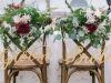 Bride and Groom Chairs at Head Table Decorated with Flowers