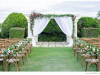 Pergola with Tied Back Fabric and Flowers with Floral Arrangements on Chairs