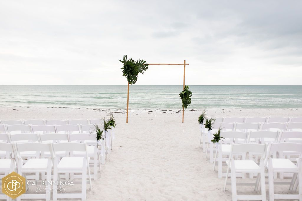 bamboo-arch-w-juat-tropical-greenery-mix-greenery-on-the-aisle-chairs
