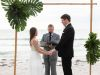 bride-groom-officiant-in-front-of-bamoo-arch-with-tropical-grns