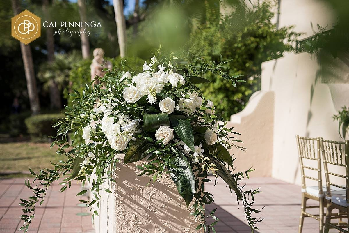 Close Up of Back of Aisle Floral Arrangement in White Flowers and Tropical Leaves