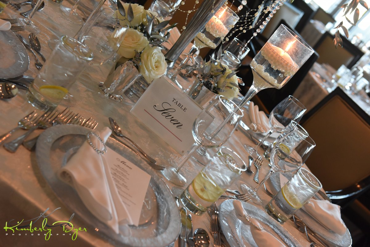 Table Setting with Footed Glass Centerpiece, Floating Candles, Loose Pearls, Rose and Silver Ruscus