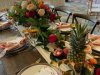 wooden-feasting-table-w-bentley-bowl-with-ranunculus-garden-roses-etc-pineapple-fruits-limes-tucked-napkins-swanky-w-menu-card