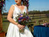 Bride with Bridal Bouquet of  protea, blue thistle, purple anemones, peach Juliette garden roses, plum stock flowers, Explorer deep burgundy open roses, deep blue delphinium, scabosia balls with Ivanhoe grevilia for greenery