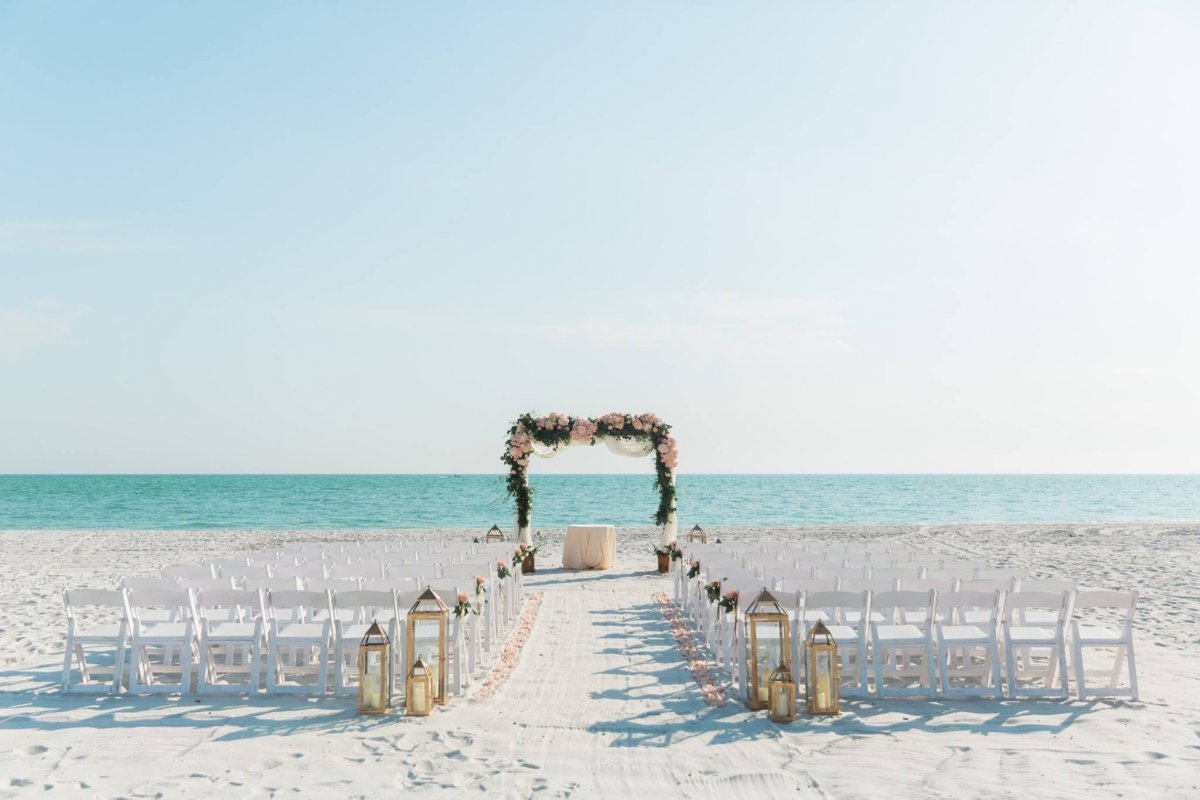 Beach Ceremony Site with Cedar Arch Draped with Fabric, Pink and Peach Flowers and Lanterns with Flowers at Back of Aisle