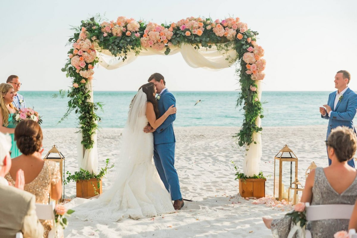 Couple Under Cedar Arch with Blush and Peach Roses, Hydrangea, Silver Dollar with Plumosa