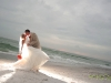 bride-and-groom-on-beach-with-coral-roses