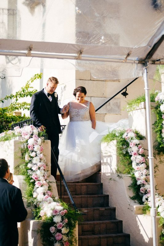 Couple Entering While Walking Down Garland Covered Stairs