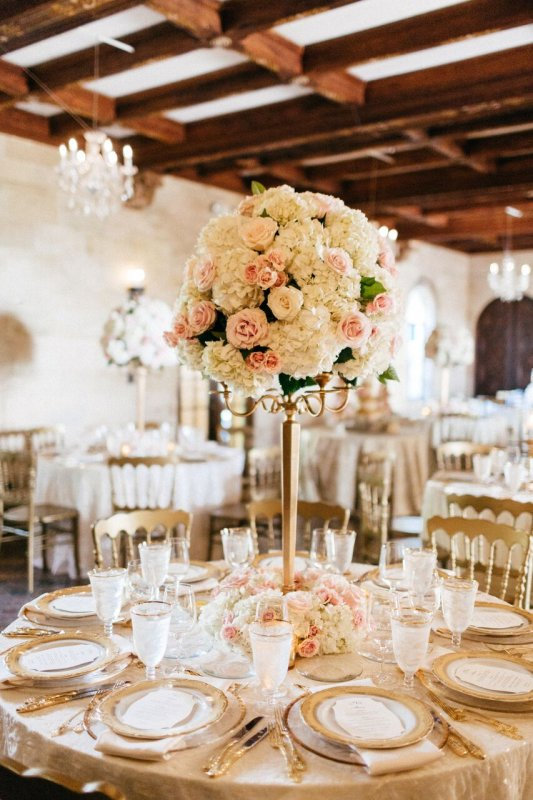 Gorgeous Guest Table Centerpiece featuring Gold Candelabra with Topiary of Hydrangea, Pink Mondial Roses, and Playa Blance White Roses with a Wreath at Base To Match