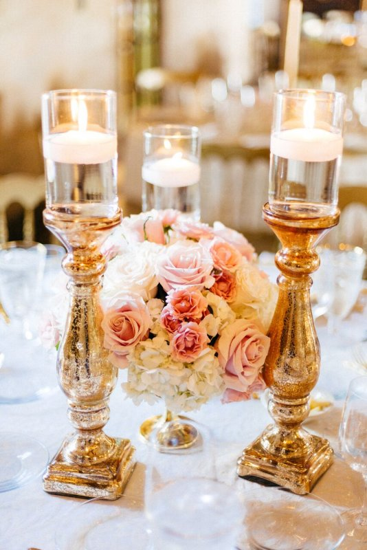 Beautiful Guest Table Centerpiece featuring a low arrangement in gold footed bowl with 3 gold pillar candle holders with floating candles