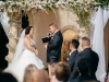 Ceremony with Bride and Groom with Flowers over head featuring Marco Polo Orchids, Hydrangea, Roses, Mums