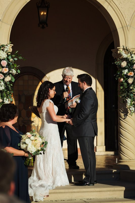 Ceremony on steps with Floral Spray Flowers to frame couple