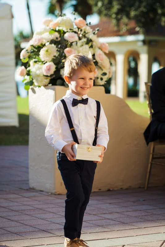 Ring Bearer  in front of Floral Arrangement at Entrance to Ceremony