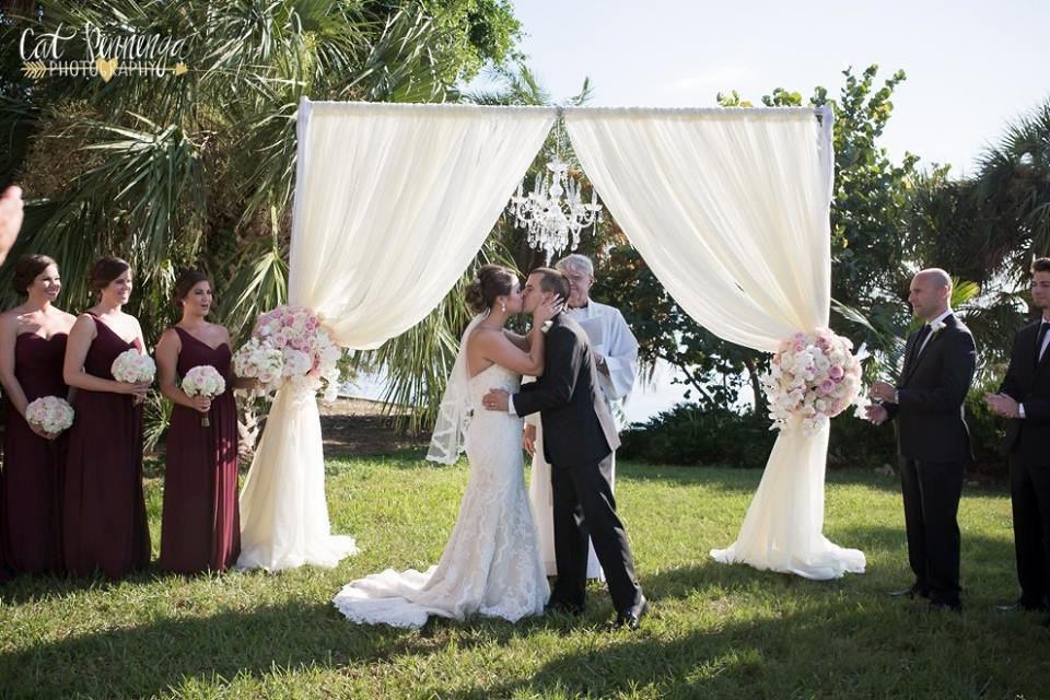 First Kiss Under the Ceremony Arch