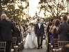 Floral Arch in Background with Greenery, Roses With Couple Walking Down the Aisle After Ceremony