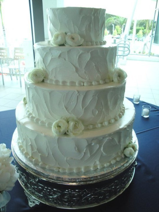 white-ranunculus on wedding cake
