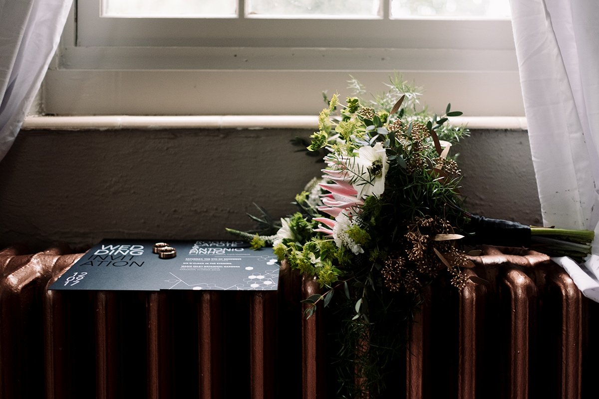 Grooms' rings, wedding invitation, and bridesmaid's bouquet