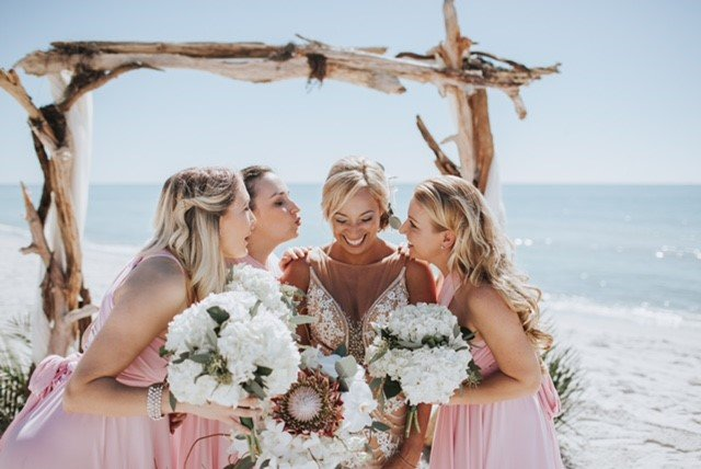 Bride and Bridesmaids under Wedding Arch on Beach