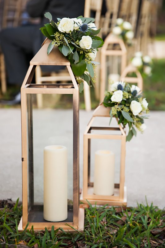 Set of Large Gold Lanterns at Back of Aisle with Candle and Flowers on Top