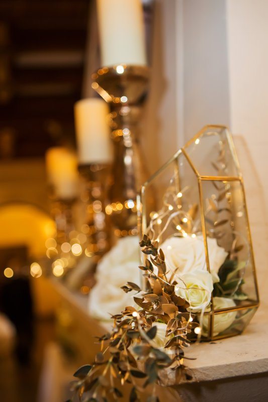 Mantle with Gold Pillar Candles and Terrarium with Flowers and Greens and Some Gold