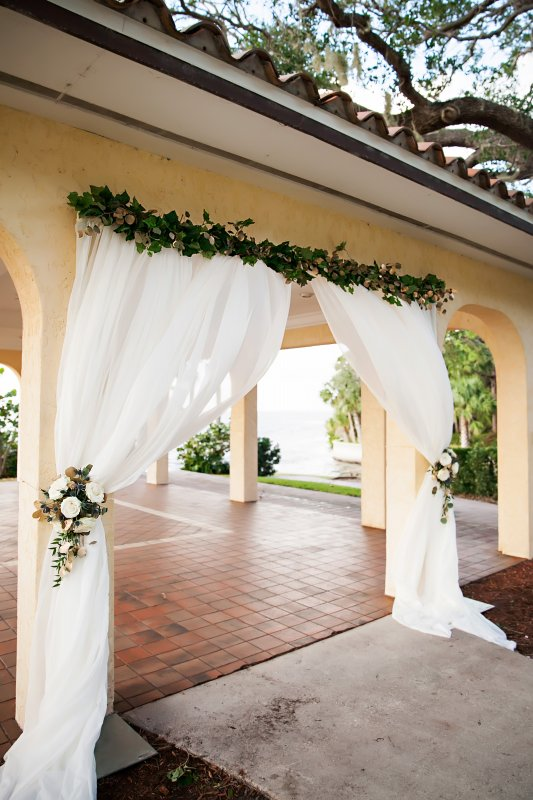 Wedding Ceremony Arch with Greens on Top and Two Floral Tie Backs