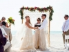 Bride and Groom with Bamboo Arch with Macrame and Garland of Tropical Leaves and Orchids