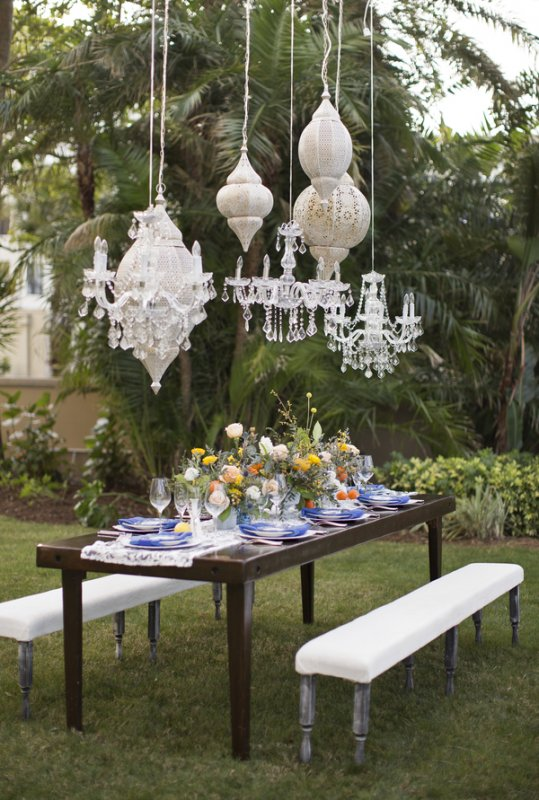 Small Wedding Feasting Table with Chandeliers and Assorted Floral Centerpieces of spring flowers and mixed vases