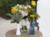 blue and milk glass filled using pin cushion protea, billy balls, ranunculus, delphinium, thistle, scabosia, hyacinths, acacia, freesia and cream, blues and yellow with the Quicksand champagne roses and the oranges for a citrus, Florida element