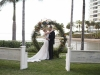 Ceremony Site natural vine standing wreath with greens and matching florals with Bride and Groom