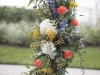 Close-up of Ceremony Site natural vine standing wreath with greens and matching florals