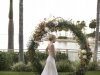 Bride near Ceremony Site with natural vine standing wreath with greens and matching florals