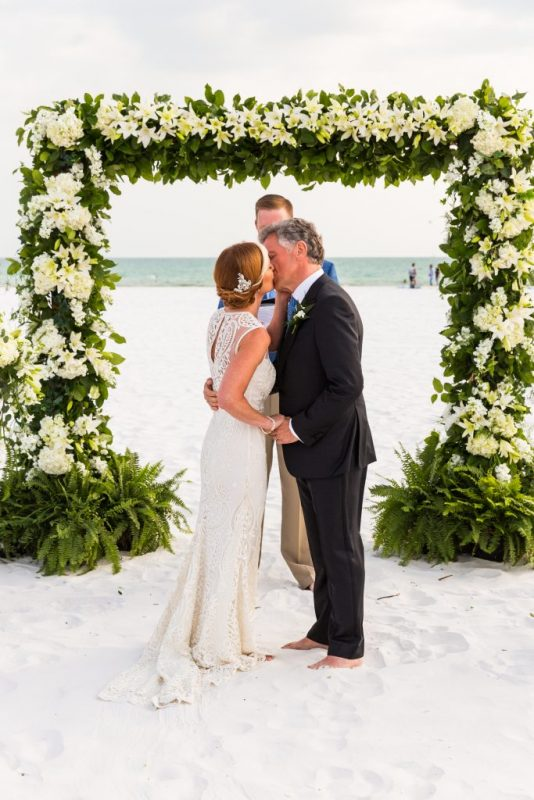 Close Up of Wedding Arch with Florals and Couples
